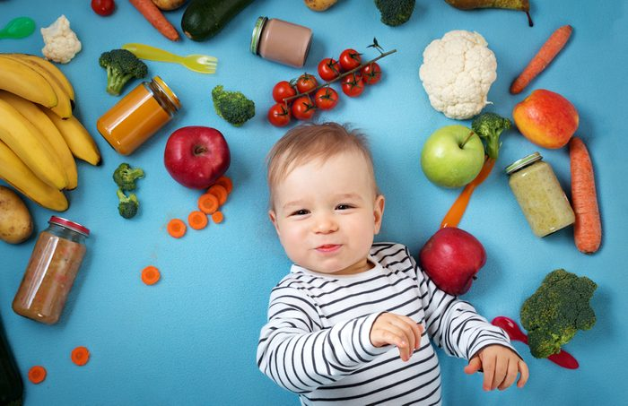 baby surrounded with fruits and vegetables on blue blanket, healthy child nutrition;