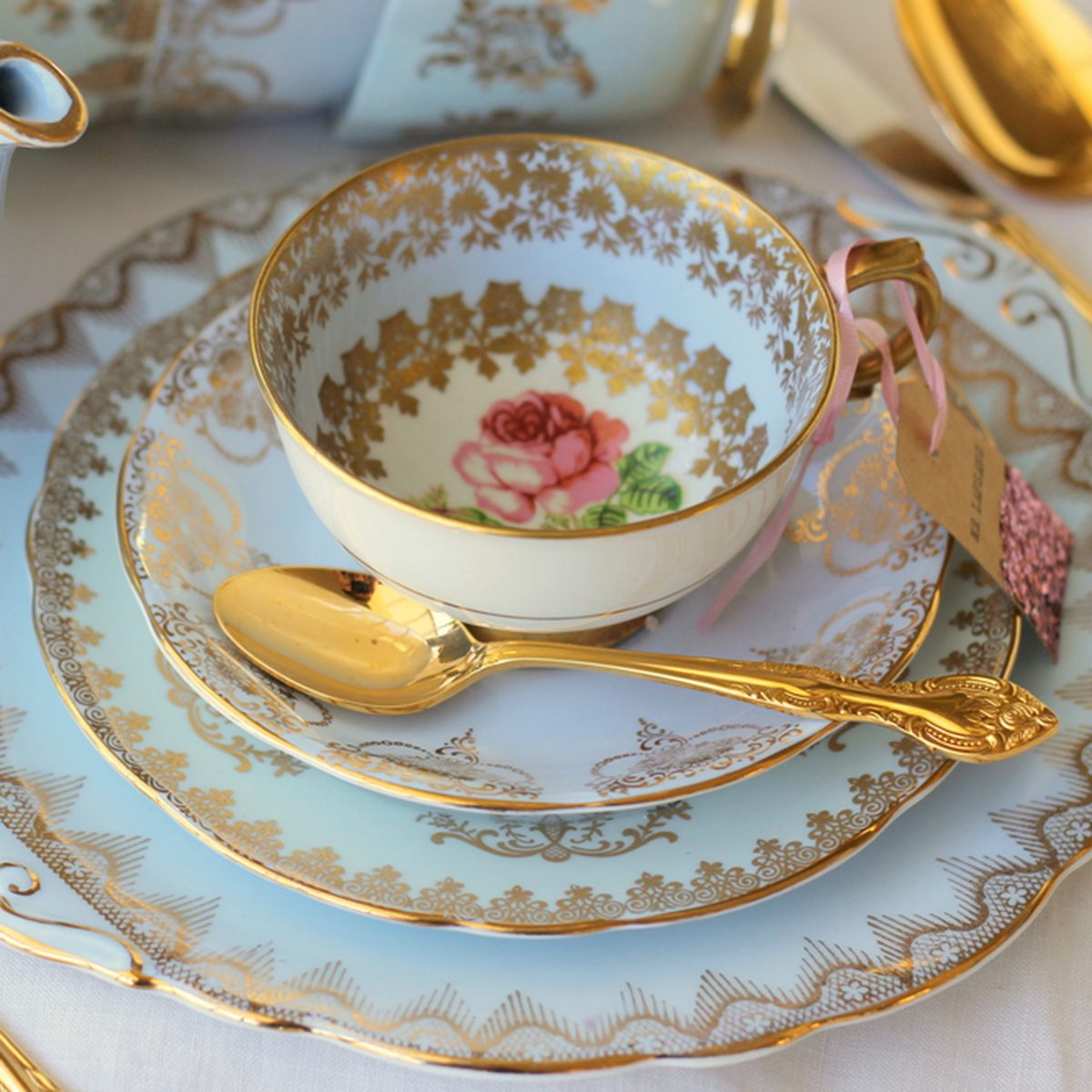 Vintage blue dinner plates, with pink rose tea cup and gold cutlery