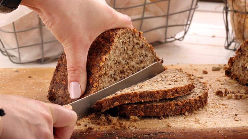 Woman cut whole grain bread on a wooden board