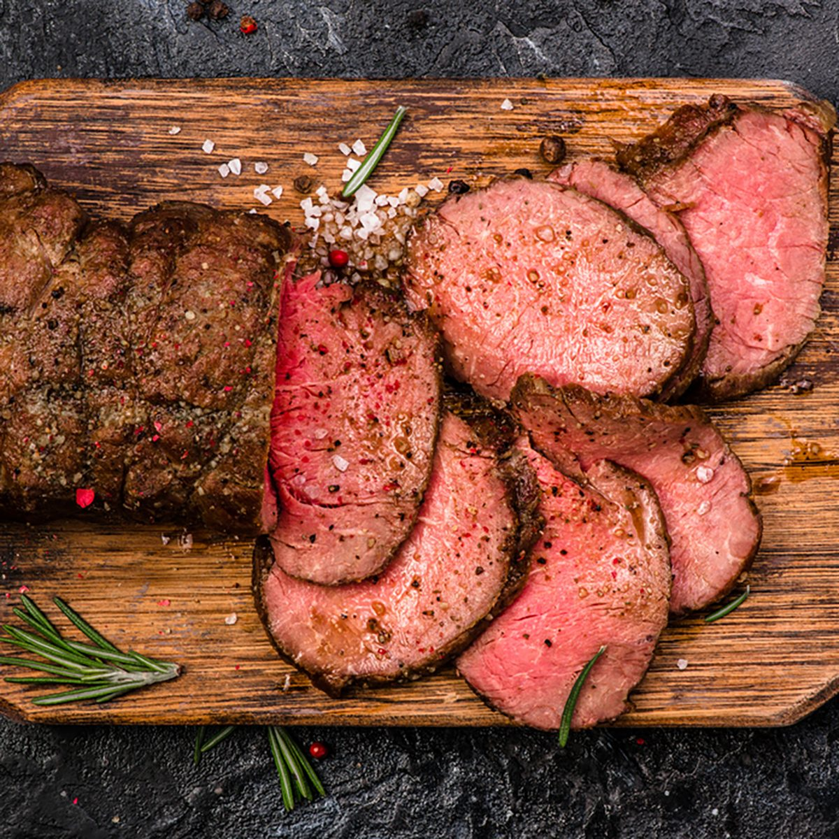 Roast beef on cutting board with salt and pepper.