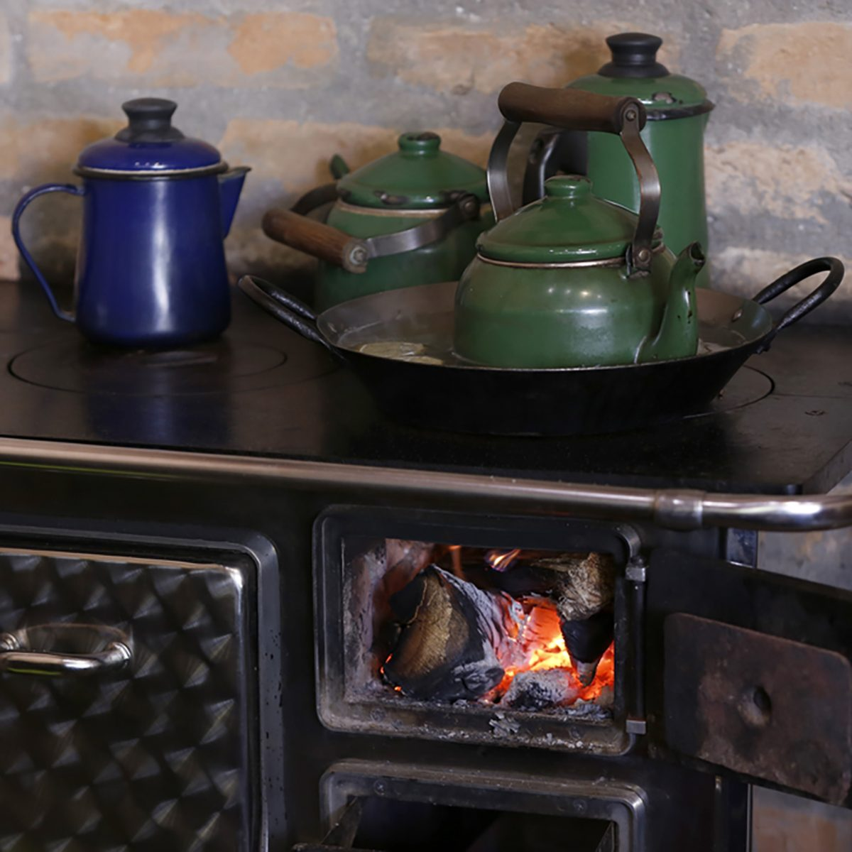 warm fire heating a coffee kettle in wood burning stove. Traditional style in countryside of Brazil