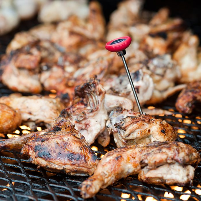 Barbecue chicken on grill with thermometer.