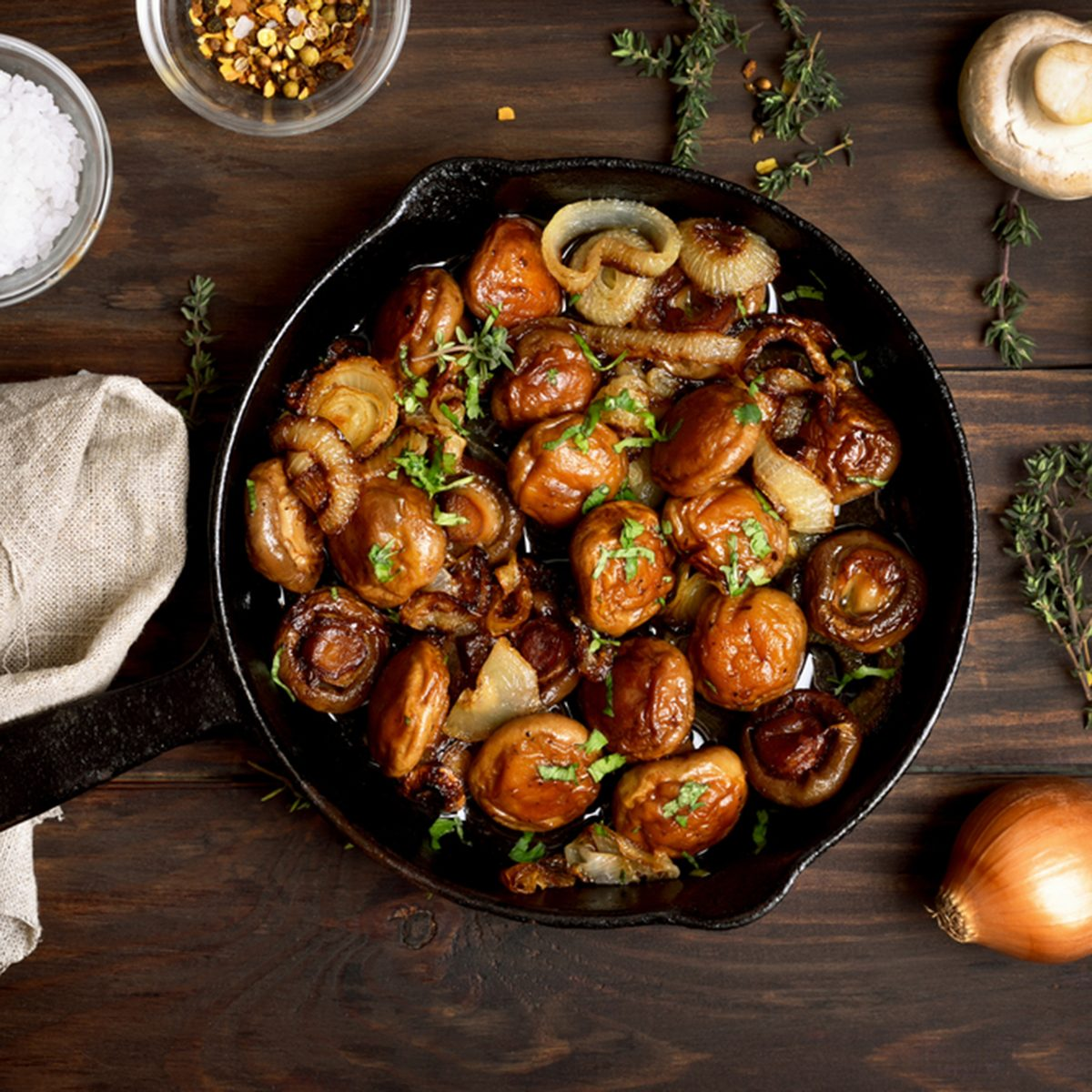 Roasted mushrooms with onion in frying pan over wooden background