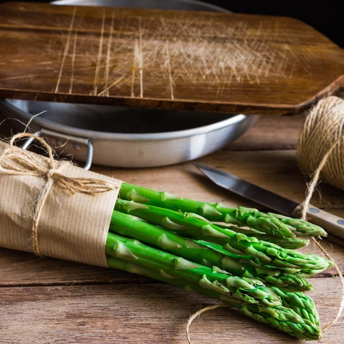 Bundle of fresh organic asparagus wrapped in craft paper on kitchen table