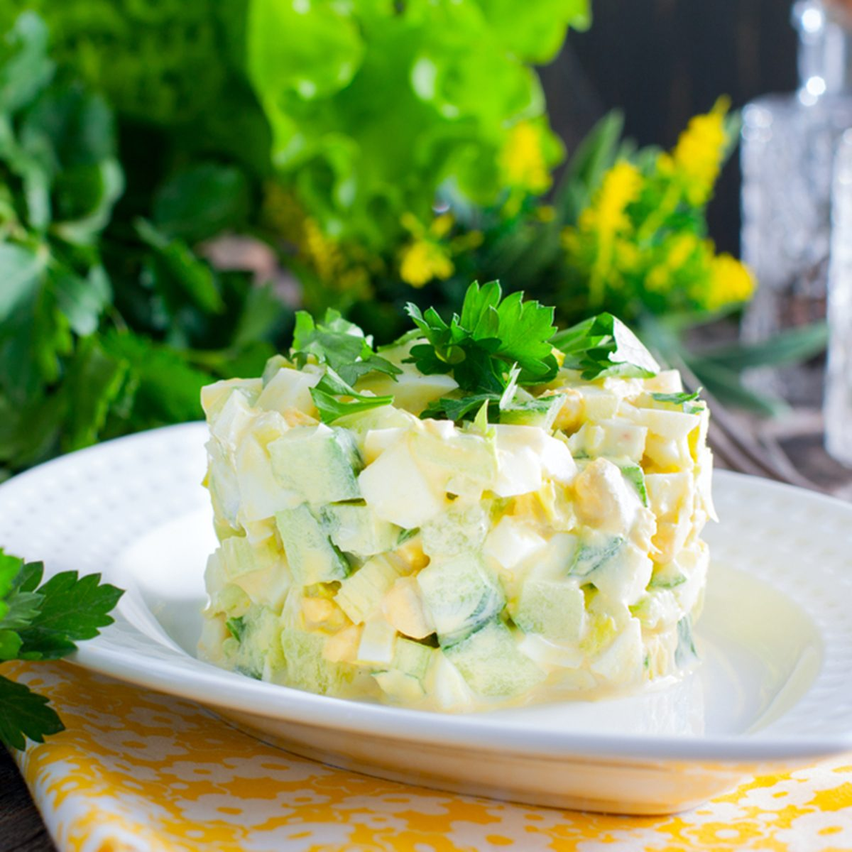 Salad with cucumber, celery and eggs on a wooden table