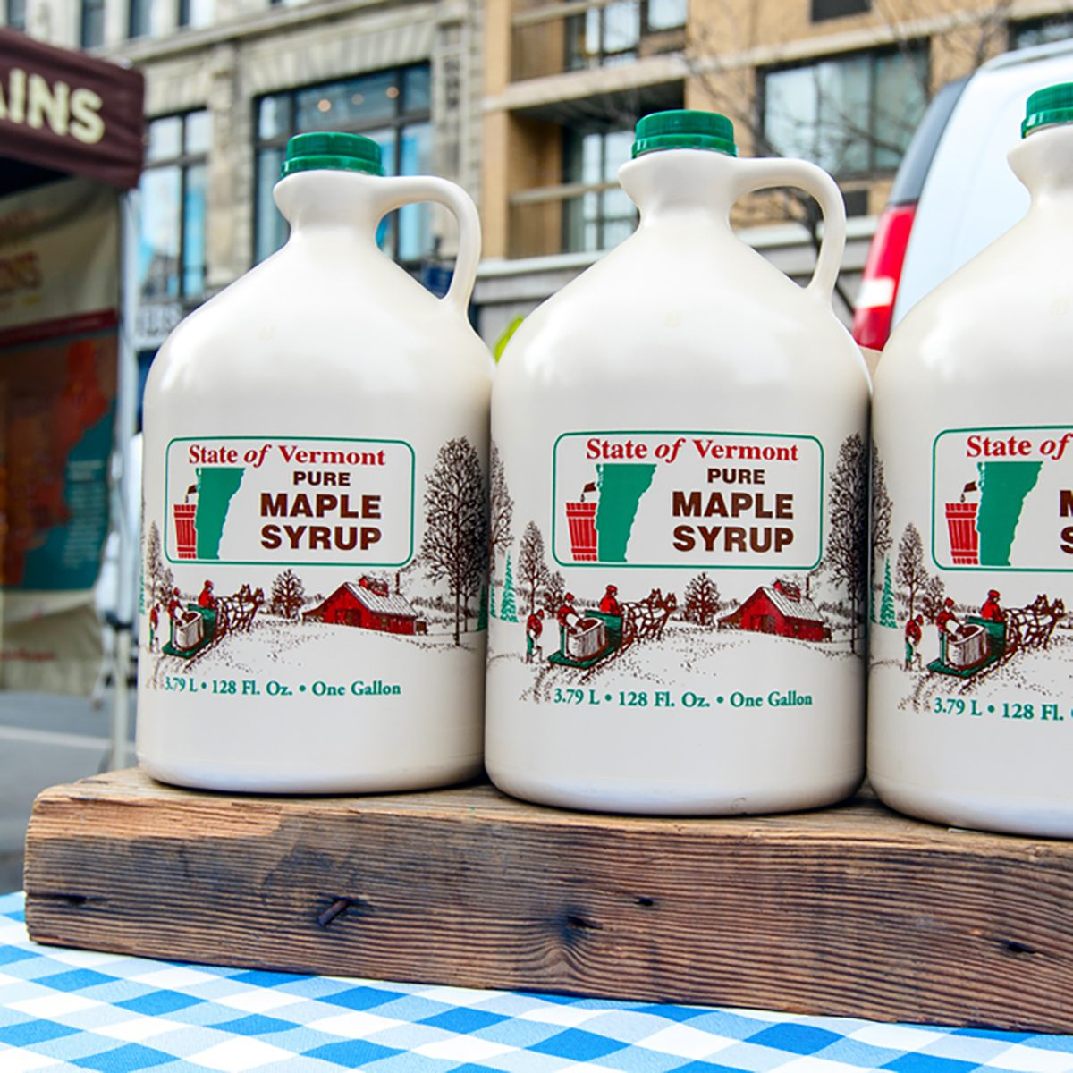 Jugs of Vermont maple syrup stand for sale at a farmer's market on Union Square