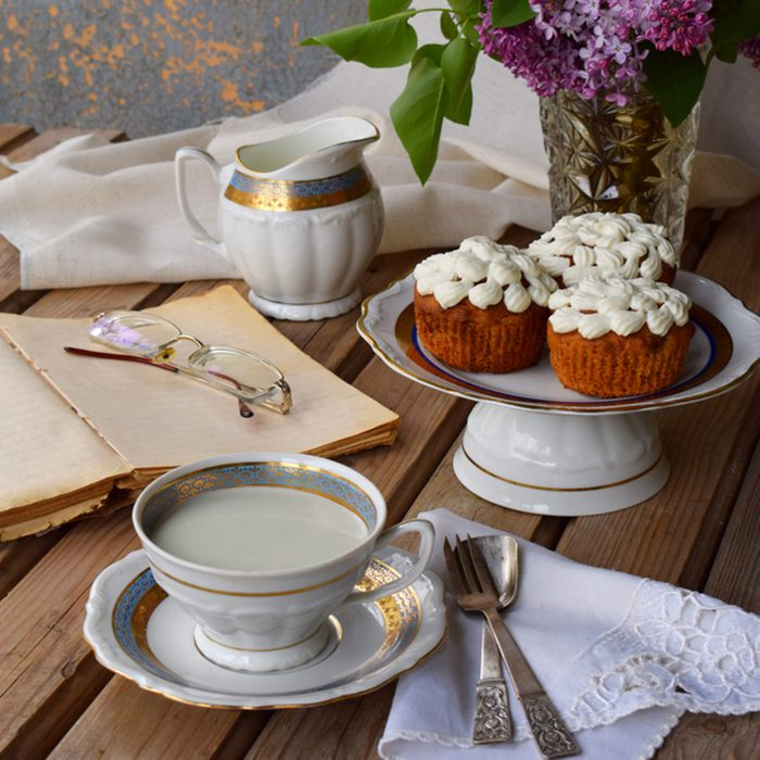 Romantic composition of bouquet white and purple lilacs, cupcakes with curd cream, cups tea with milk, old book on wooden background.