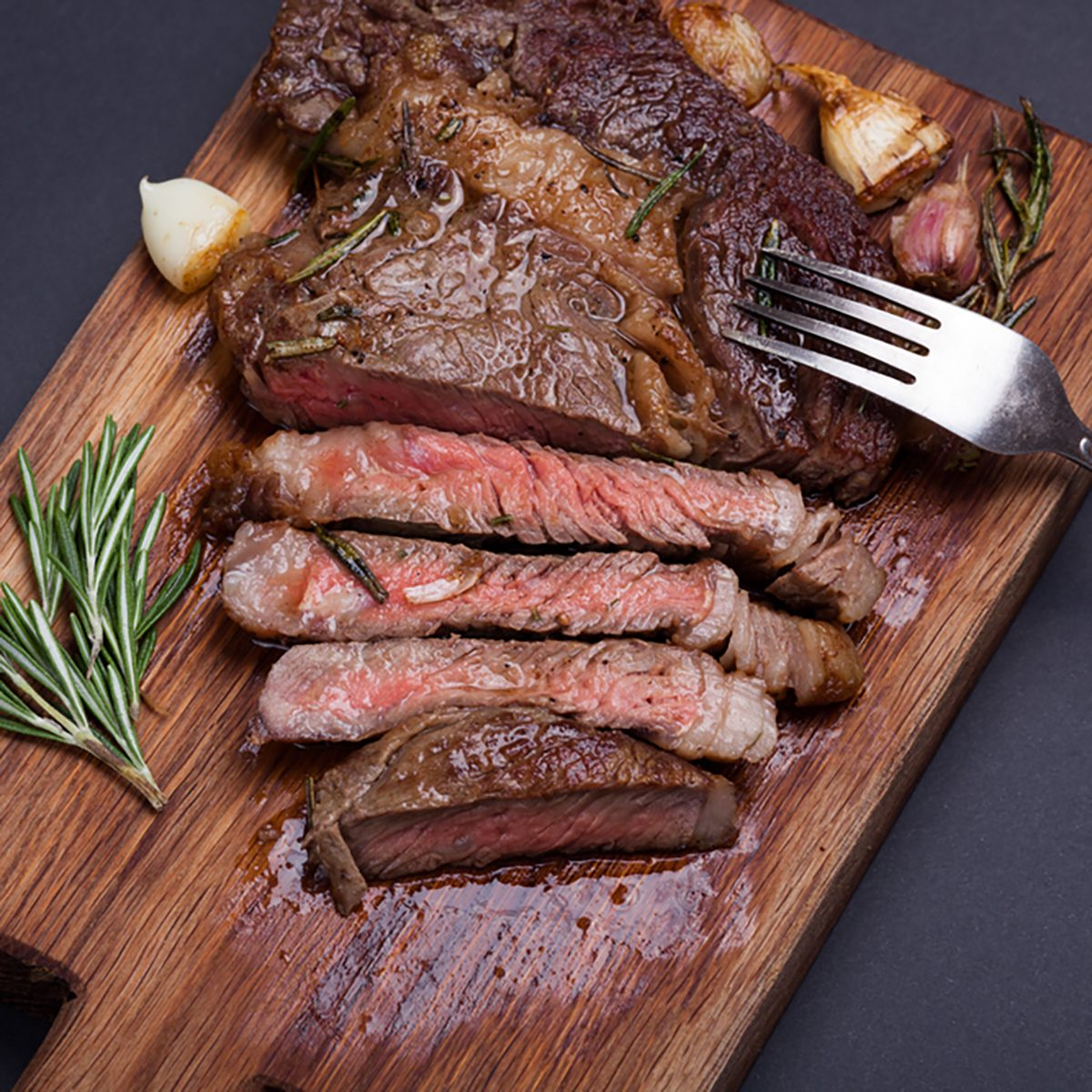 Grilled ribeye steak of marble beef closeup with spices on a wooden Board. Juicy steak medium sliced and ready to eat.