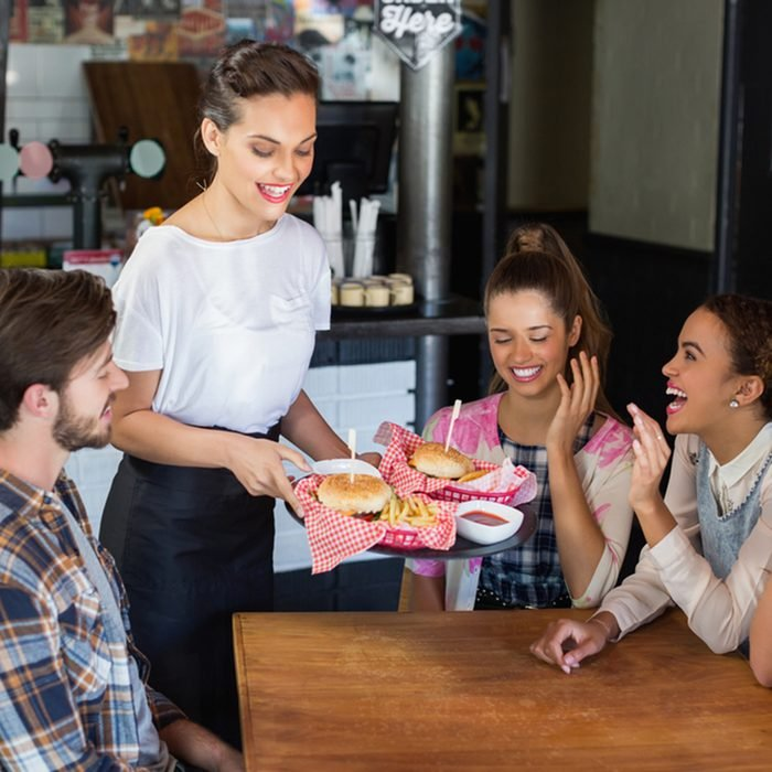 Waitress serving burgers to cheerful customers in restaurant