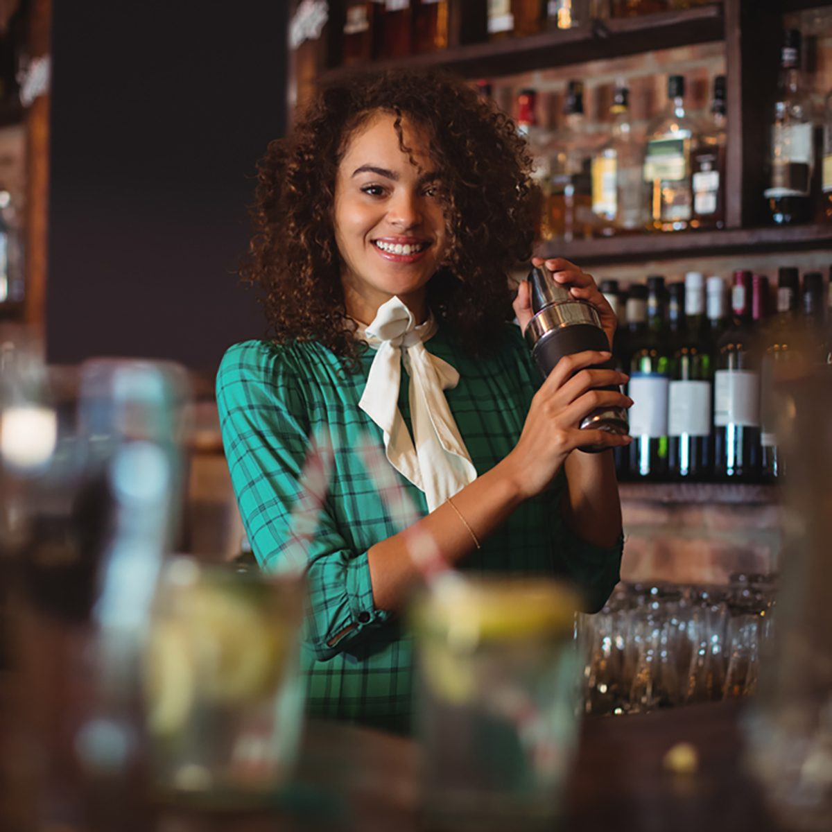 Portrait of female bartender mixing a cocktail drink in cocktail shaker at counter
