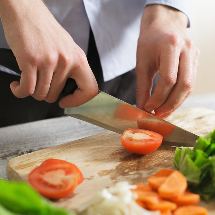Close up of male hand cutting tomato on cutting board with sharp knife