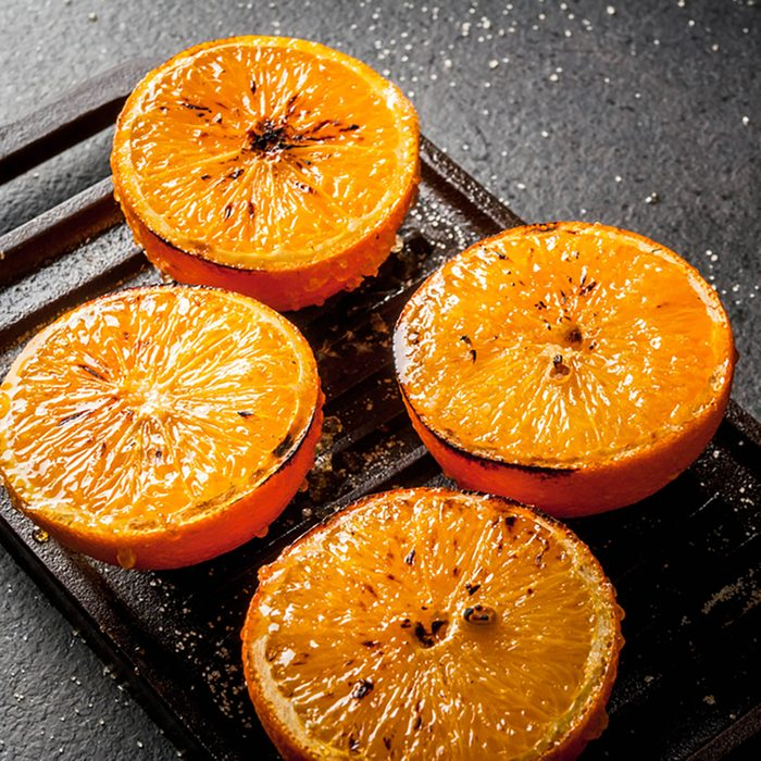 Ideas for a healthy dietary vegan breakfast. Paleo diet. Grilled oranges grapefruits. In the grill pan on a black stone table.