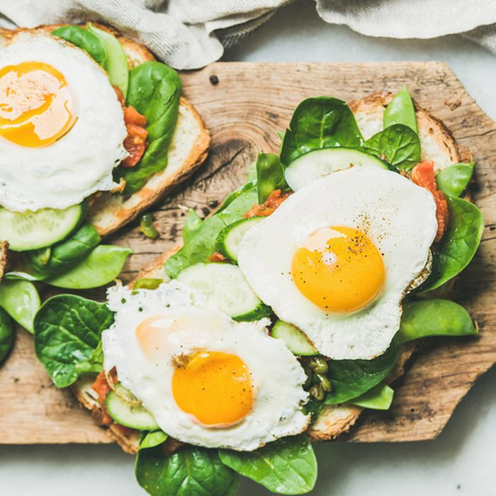 Bread toasts with fried eggs and fresh vegetables on rustic wooden board over grey marble background, top view.