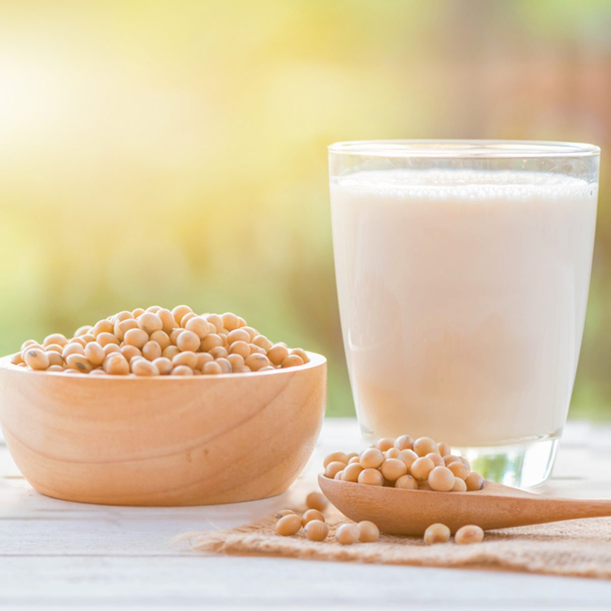 Soy milk in glass and soy bean on spoon it on white table background with lighting in the morning
