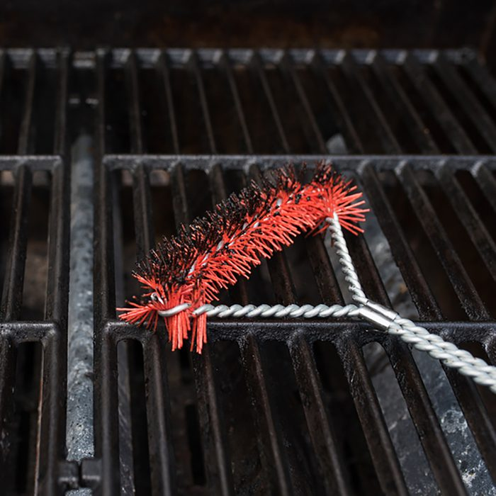 Close up focus of a scrubbing utensil used for cleaning a dirty grill.