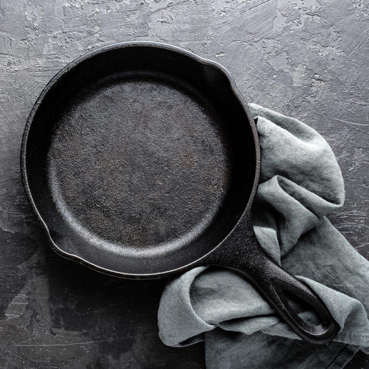 Empty cast iron frying pan on dark grey culinary background