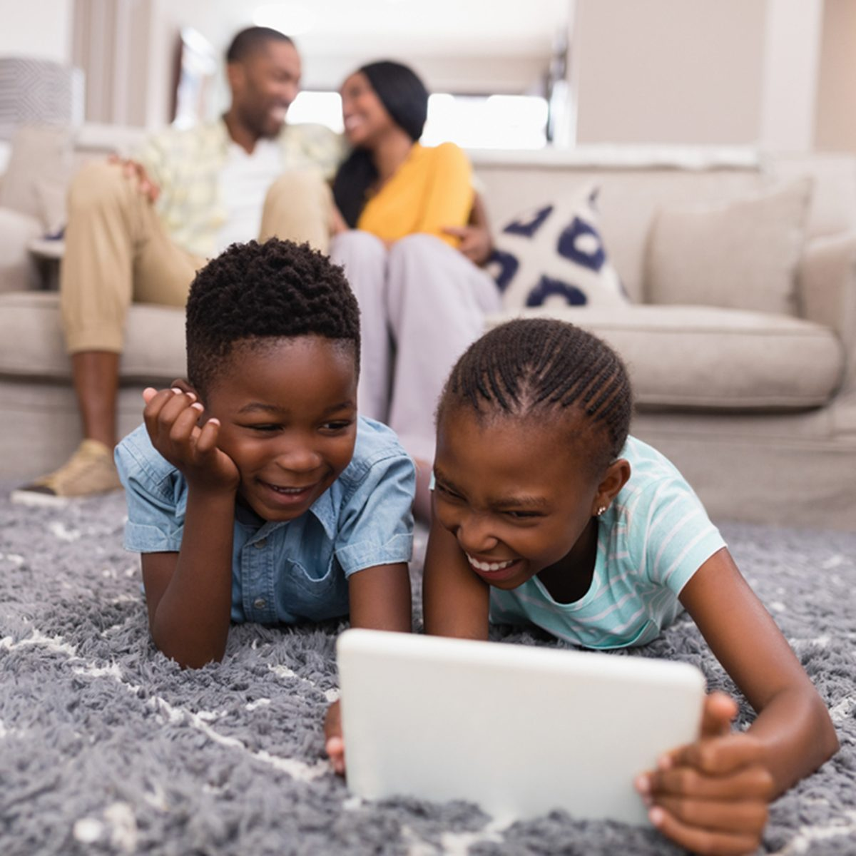 Smiling children using digital tablet while parents siting on sofa at home
