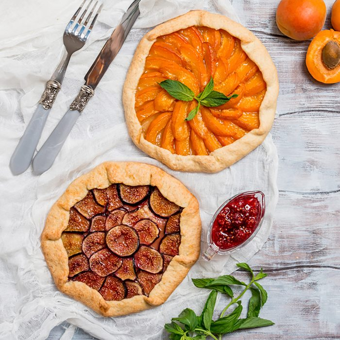 Homemade apricot and figs galette made with fresh organic apricotes and fig jam on wooden table.
