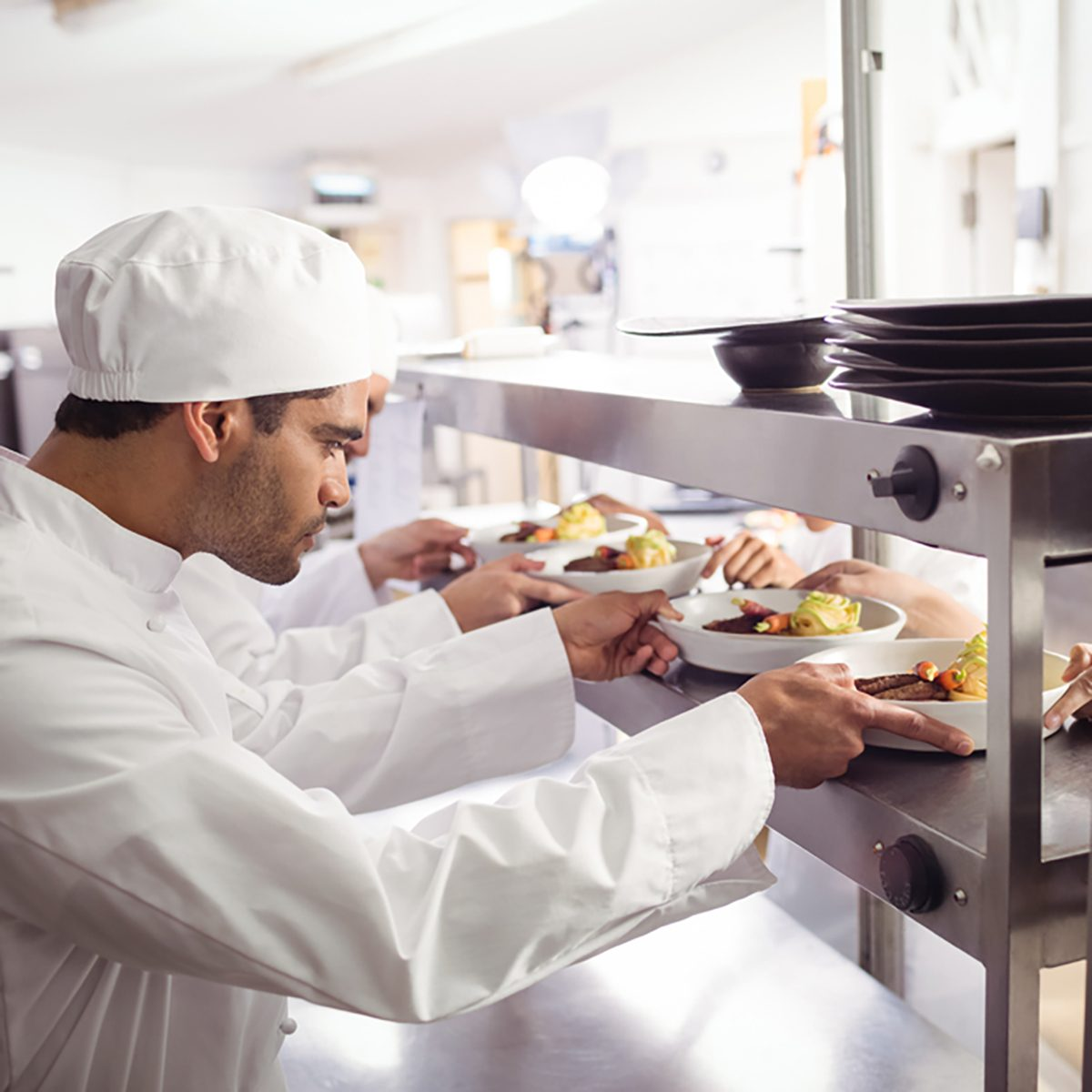 Chefs passing ready food to waiter at order station in commercial kitchen