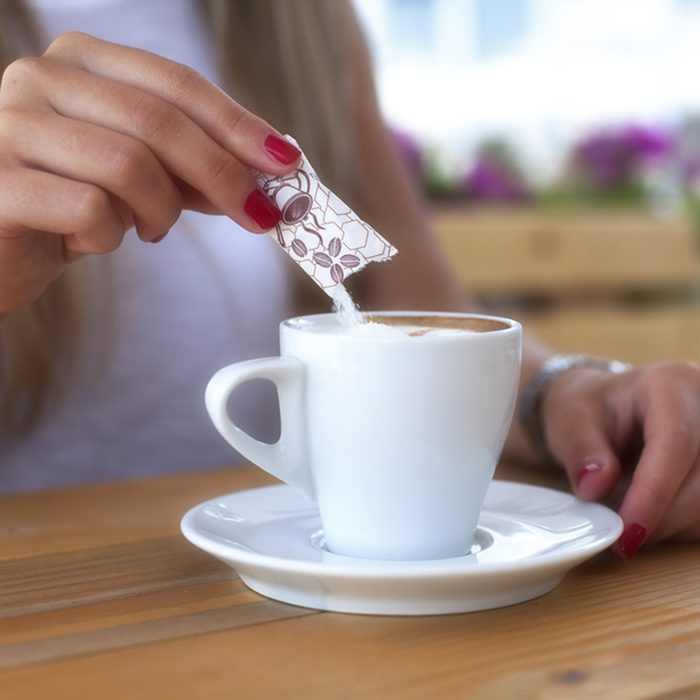 Young woman adding sugar to the coffee