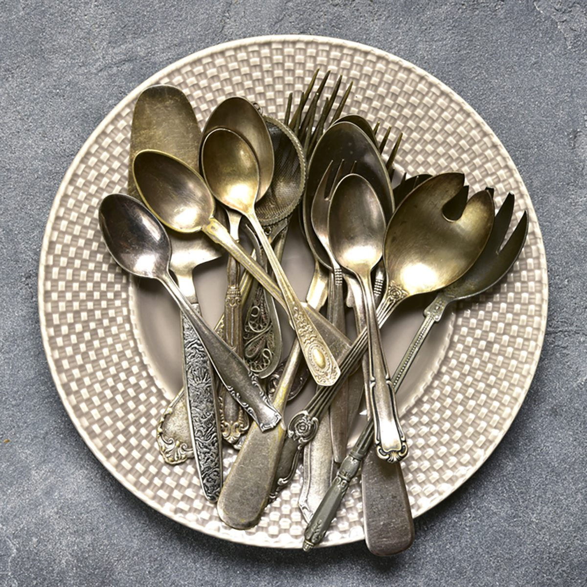 Vintage silverware on a plate over dark grey slate,stone or concrete background.
