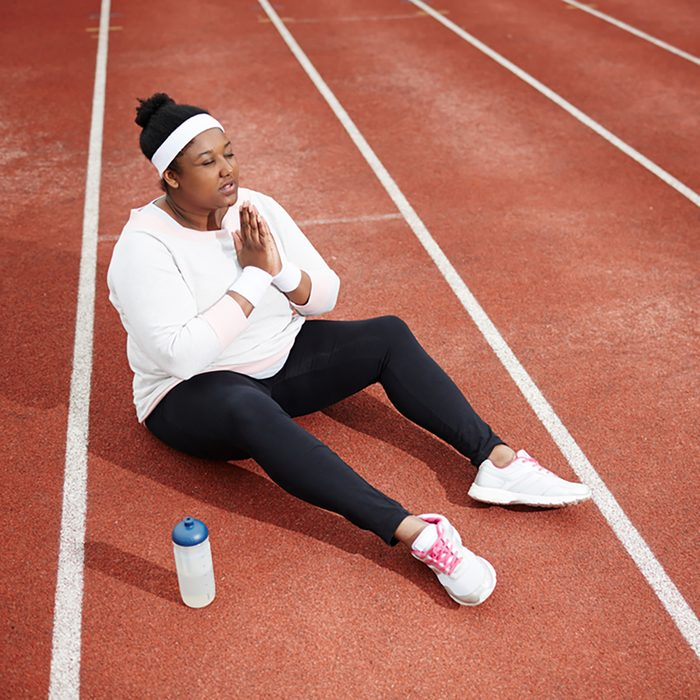 Religious and active plump female in sportswear asking Lord to bless her for workout while sitting on racetrack of stadium