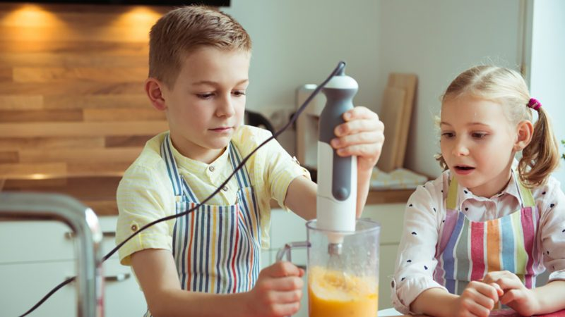 Portrait of two happy and cute little children which having fun during preparing muffins with blender in modern kitchen