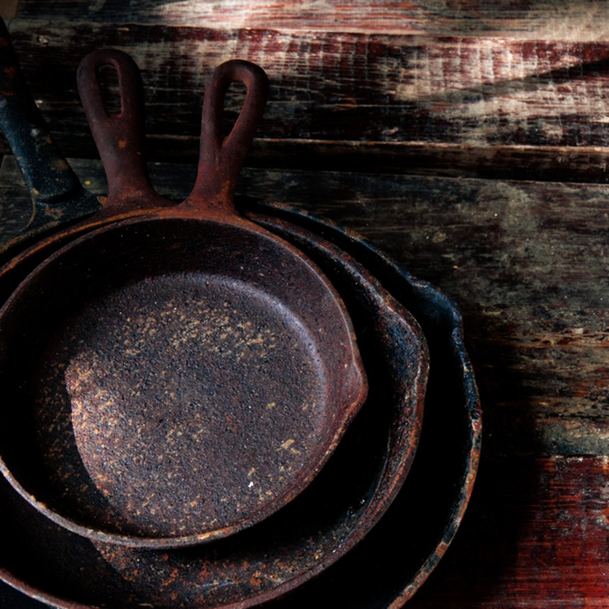 a stack of three cast iron skillets