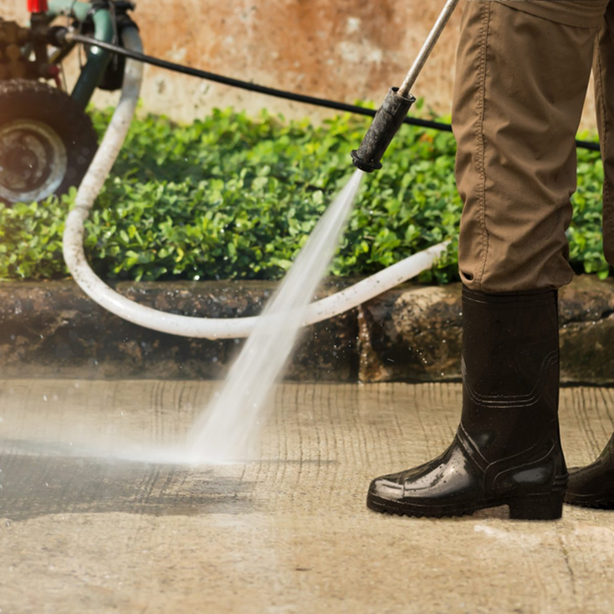 Worker cleaning driveway with gasoline high pressure washer splashing the dirt