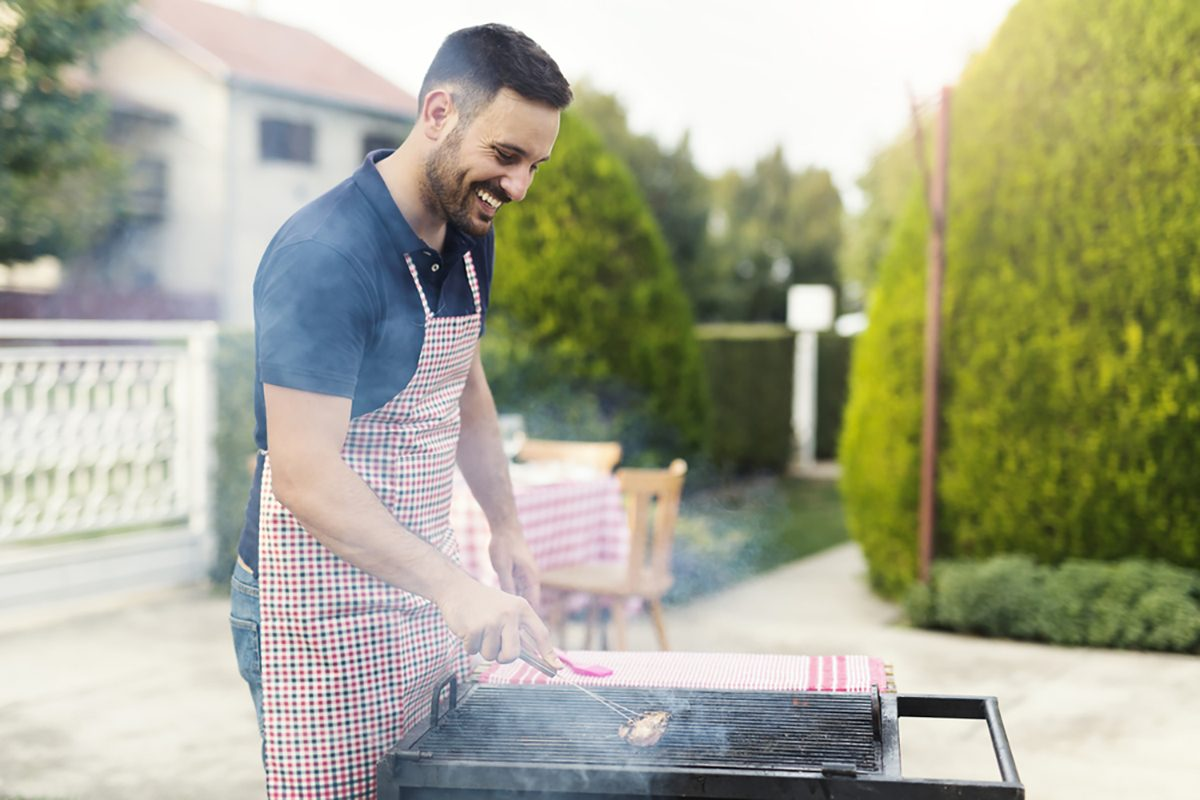 Young handsome chef smiling and cleaning grill
