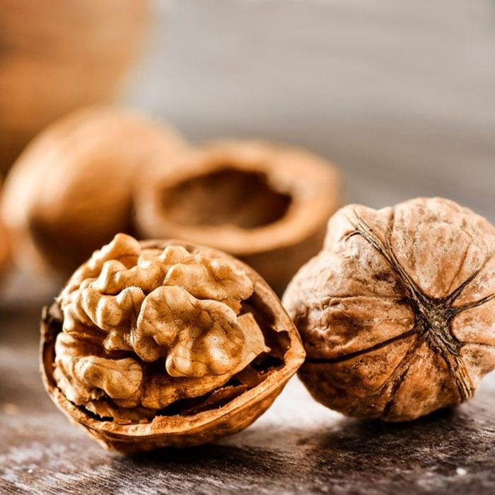 Walnuts kernels on dark desk with color background