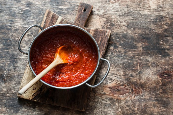 Classic homemade tomato sauce in the pan on a wooden chopping board on brown background, top view.