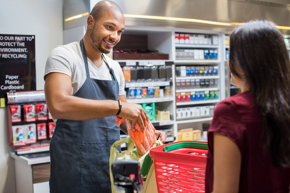 Smiling salesman putting vegetables in bag for customer after billing. Cashier black man at grocery store helping customer pack purchased products. Happy young man working in grocery shop.; Shutterstock ID 768054214; Job (TFH, TOH, RD, BNB, CWM, CM): TOH Grocery Shopping Secrets