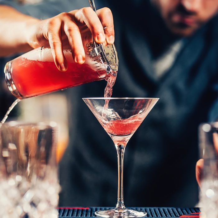 Close up details of barman pouring vodka cosmopolitan cocktail in martini glass;