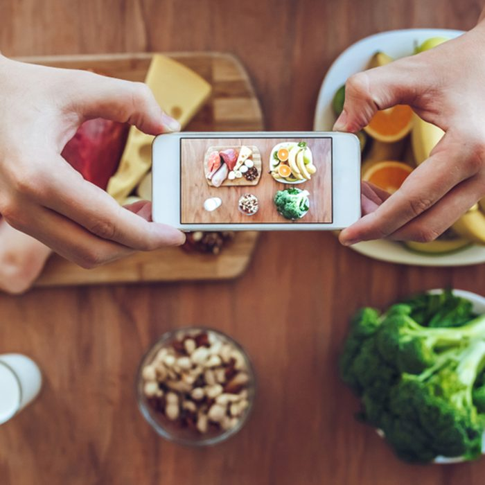 Top view of meat, fish, fruits, vegetables, nuts, milk are lying on the table while man is taking photo of it on a smart phone.