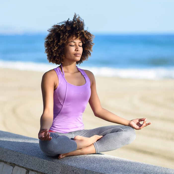 Black woman, afro hairstyle, doing yoga asana in the beach with eyes closed.