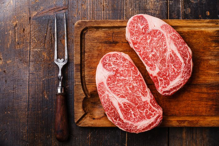 Raw fresh marbled meat Steak Ribeye Black Angus and meat fork on wooden background copy space; Shutterstock ID 651752392