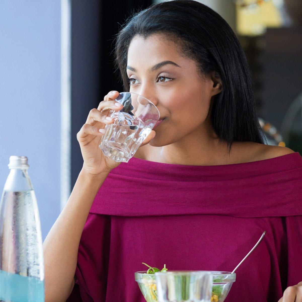 African girl drinking water during her lunch break at restaurant.