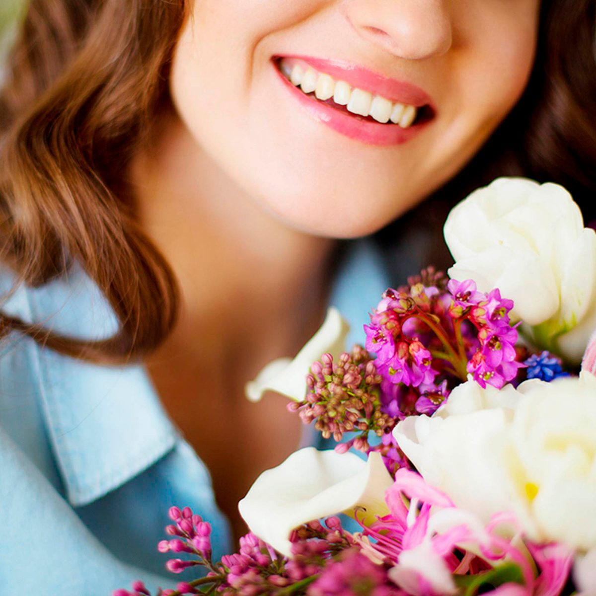 Woman smiling while holding flowers