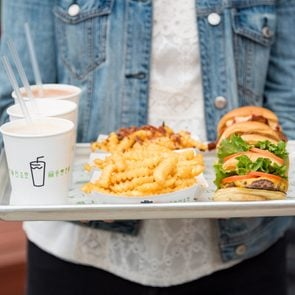 Person carrying tray of Shake Shack food