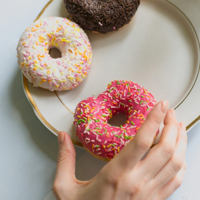 Donuts on a plate with a hand reaching towards them