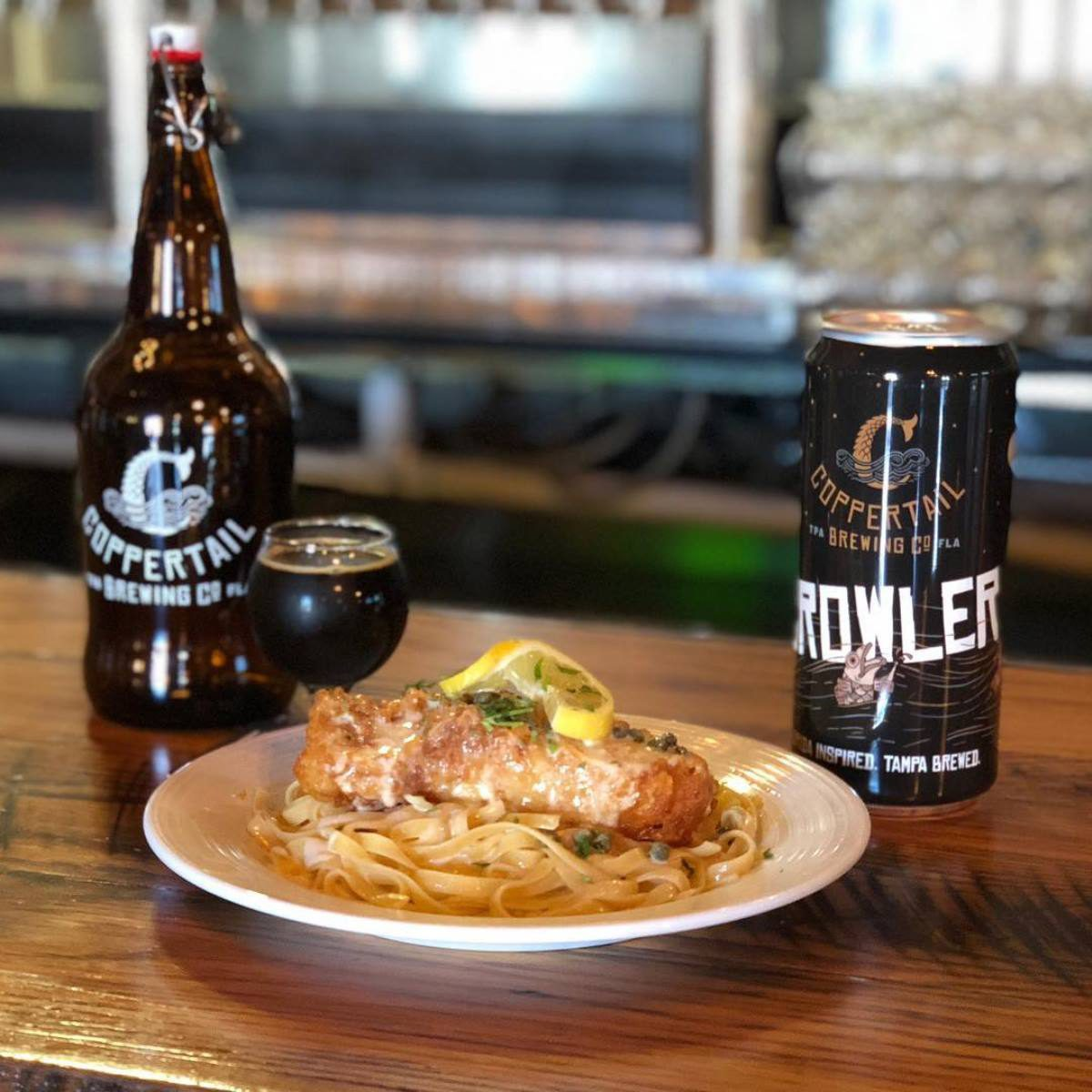 Beer and fried fish over noodles at Coppertail Brewing