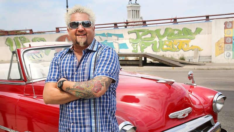 Guy Fieri standing in front of red car