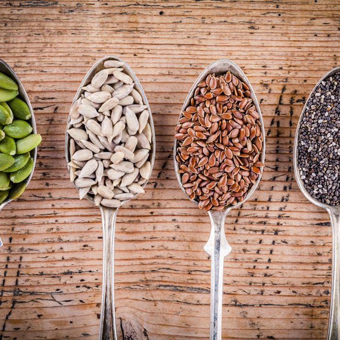 Healthy superfood: pumpkin seeds, sunflower seeds, flax seeds and chia on wooden table