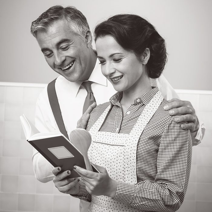 Vintage wife and husband reading a cookbook together at home