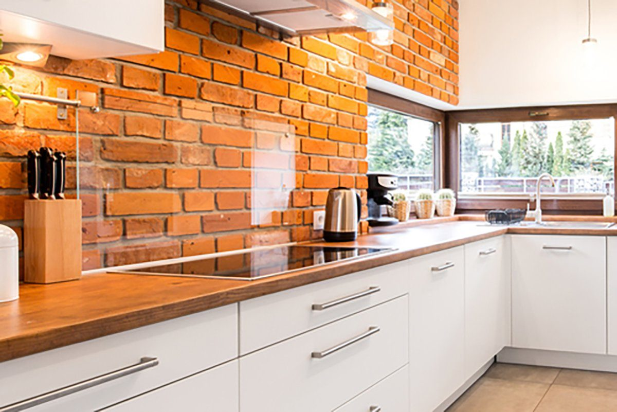 Kitchen with a brick backdrop instead of tile