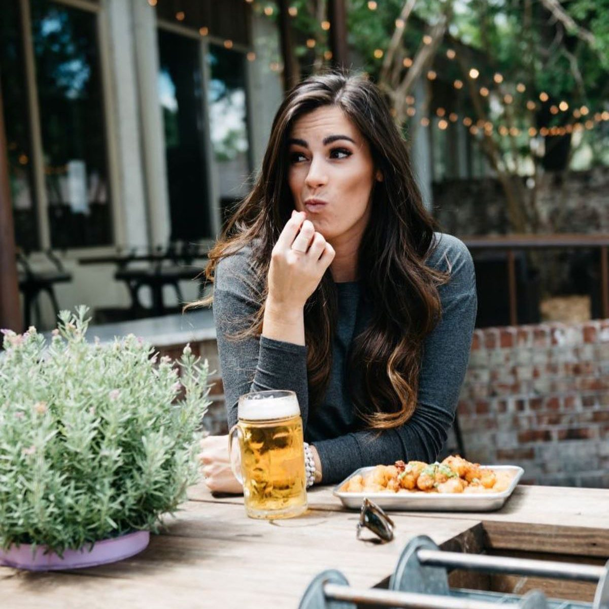 Woman enjoying a beer and appetizer at Bay Street Biergarten's beer garden