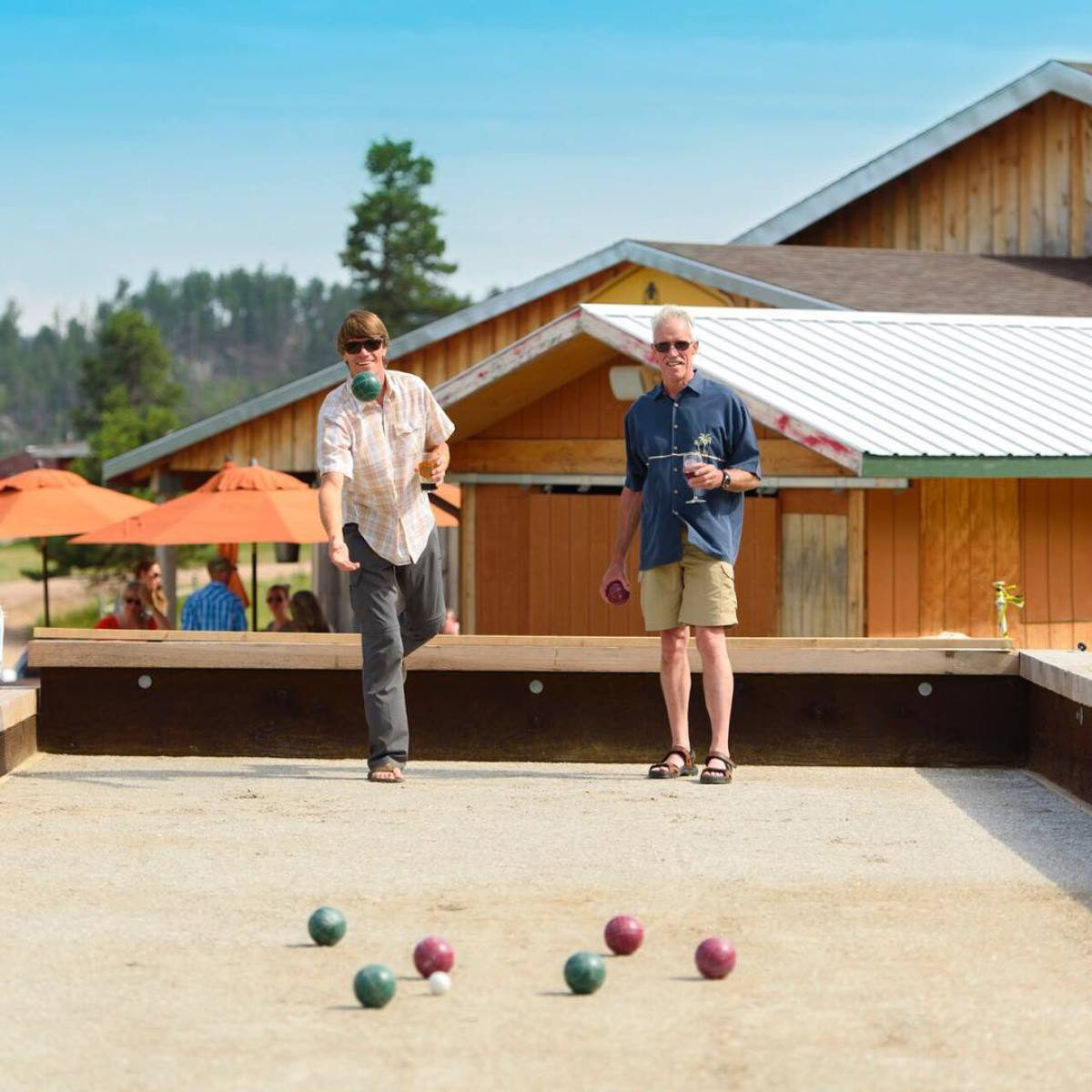 Two men enjoying a ball toss game and wine at Miner Brewing