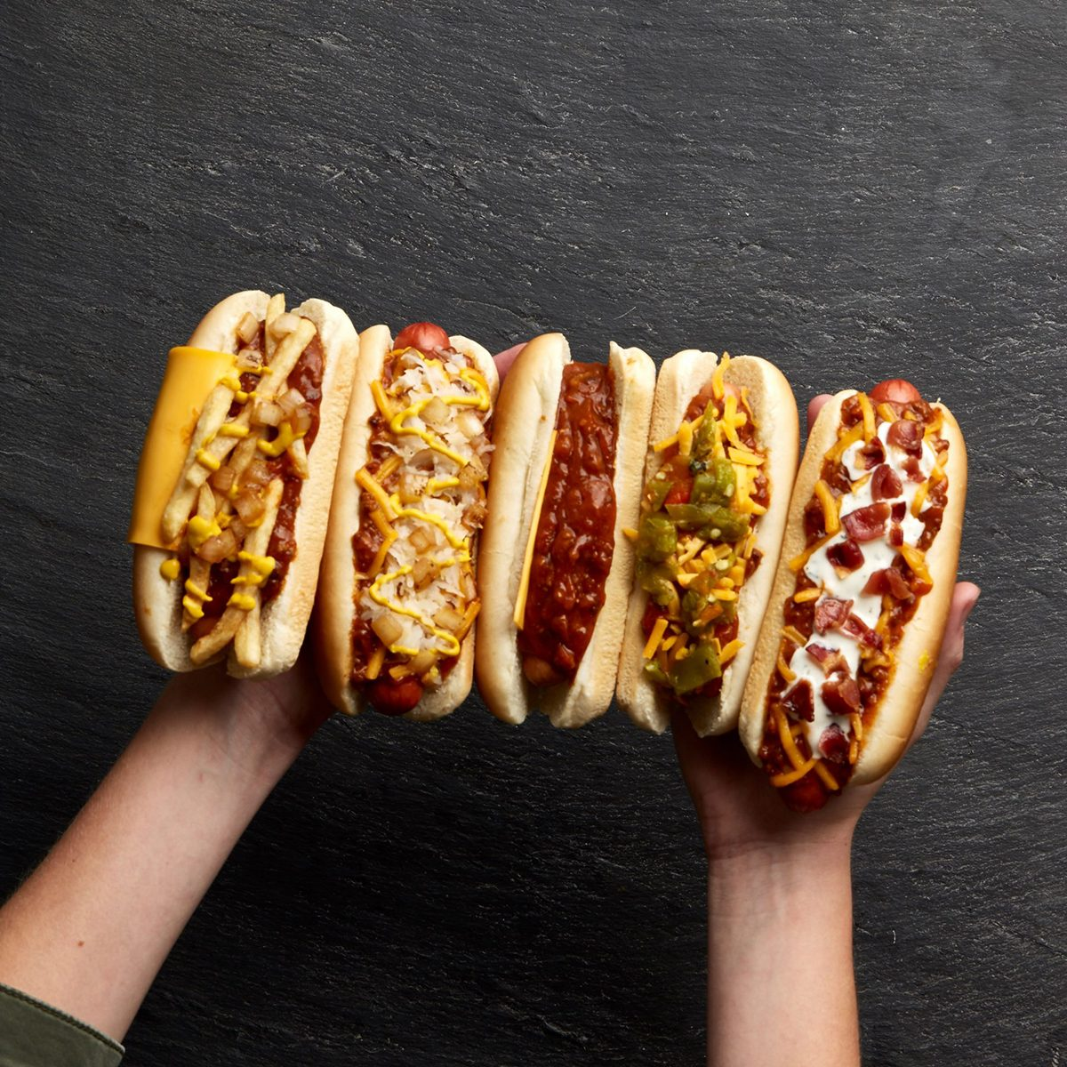 Two hands full of hotdogs