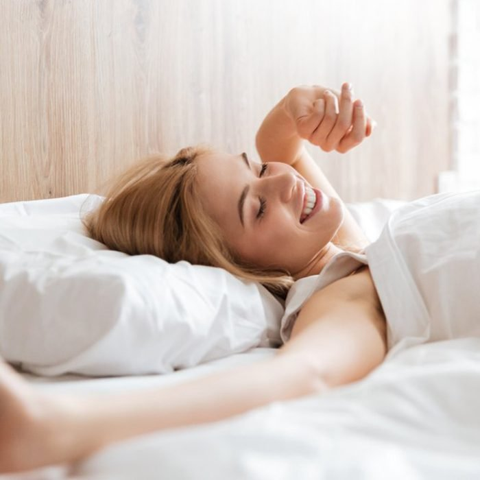 Woman waking up and stretching in bed